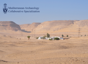 Blue sky atop desert sands with a small village of white buildings in the centre