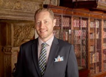 John McQuillen standing in front of bookshelf